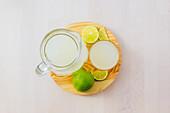 Homemade refreshing lemonade in server in glasses on wooden tray