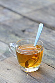 Herb tea in a glass cup with a spoon
