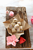 Gluten-free layered biscuits with pink icing and pink paper flowers on a rustic wooden board