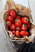 Fresh vine tomatoes in a paper bag in a wooden basket