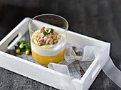 Vegan pineapple, mango and coconut dessert in a glass with fruit pudding, coconut cream, lemon curd and baked almond crumbles