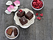 Vegan sweets made with chickpeas, almonds and dates with chocolate glaze and garnished with dried raspberries or sea salt