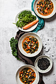 Bowls with yummy kale soup with carrot and black seeds placed on gray table near napkins