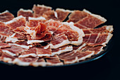 thin slices of ham with tallow lines served in plate on black background
