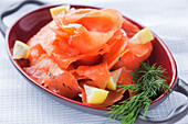Slices of fresh salmon with pieces of lemon and aromatic dill placed on plate