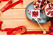 Stilleben mit Granatapfel und leuchtend rotem Samtband