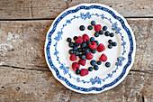 Blaubeeren und Himbeeren auf Vintage-Teller
