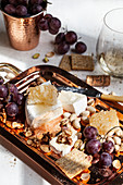 A cheeseboard with brie topped with honeycomb, crackers, walnuts, pistachios, grapes and white wine