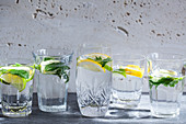 Various water glasses filled with lemons, limes, mint and ginger