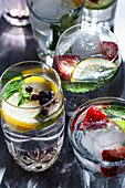 Various glasses of water filled with fruit, mint and ginger