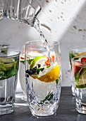 Various glasses of water filled with fruit, mint, and ginger with water being poured from a pitcher into one glass
