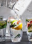 Verschiedene Gläser aromatisiertes Wasser mit Obst, Minze und Ingwer