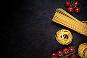 Bunch of uncooked pasta and ripe cherry tomatoes placed on black background