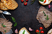 Various palatable Italian dishes and cooking ingredients arranged in frame on black background