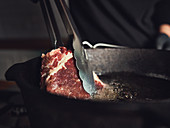 Frying a steak in a pan