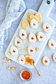 Easter egg cookies with apricot jam on a marble cutting board