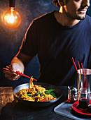 Mann isst asiatisches Stirfry-Nudelgericht mit Stäbchen
