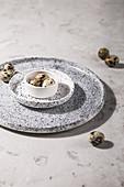 Wachteleier in Schälchen auf gesprenkelten Tellern