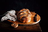 Challah bread with sesame seeds on a rustic wooden board
