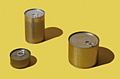 Three different tins on a yellow surface