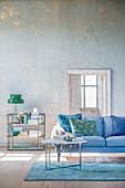 Wohnzimmer in Blau- und Grüntönen mit abgenutzter Wand