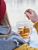 A woman wearing winter clothing holding a cup of tea