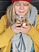 A woman wearing winter clothing holding a warm cup of tea