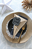 Handmade paper cone with motto on Christmas place setting with golden plate