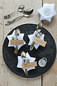 Place cards made from DIY origami stars and antique spoons