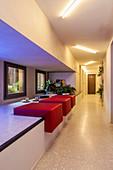 Vielfältig nutzbare Ablagefläche mit roten Ledersitzen vor Fenster