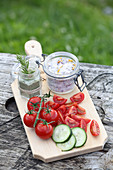 Tomatoes and cucumber with homemade herb salt on a wooden board