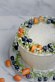 A cream cheese cake decorated with kumquats, blueberries and flowers