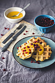 Waffles with mango mousse and pomegranate seeds