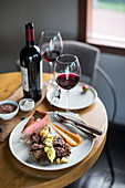 Rindfleisch mit Sauce, Beilagen und Rotwein auf Restauranttisch