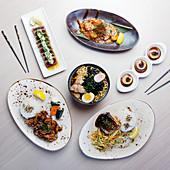 Auswahl von modernen japanischen Gerichten (Hähnchen-Ramen, Thunfisch-Tataki, Soba-Hähnchen, Ebi-Chili-Sauce, Gegrillter Lachs und Jakobsmuscheln mit Misosauce)