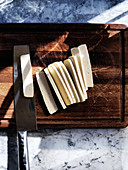 Slicing fresh pressed tofu on a dark wooden board