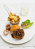 Pulled pork in a white roll with barbeque sauce, served with chunky chips with melted cheese, a pot of tomato relish and a green salad