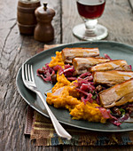 Pork belly on a bed of sweet potato mash, red cabbage with gravy