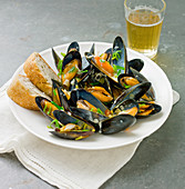 A pint of muscles in their shells, in a white bowl with crusty French bread and a glss of beer