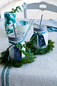 Drinks in jars with straws and screw-top lids, wreaths of pine and mottoes