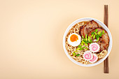 Top view of Japanese noodle soup ramen in white bowl with noodles, meat broth, sliced roasted pork, narutomaki, egg with yolk on pastel beige background