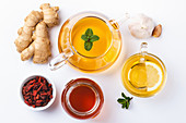 Homemade ginger and lemon tea, honey, goji, garlic, white background