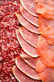 Slices of smoked salmon, salami and ham