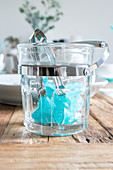 Blue ice cubes and tongs in transparent ice bucket