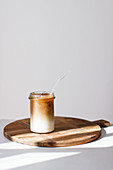 Ice coffee on a wooden board against a white background