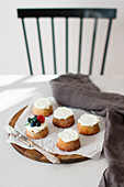 Cardamom and marzipan cakes topped with cream and berries