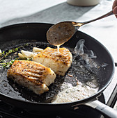 Butter basted fish fillets with garlic and thyme