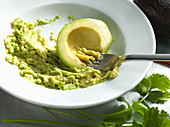 An avocado being mashed