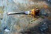Spaghetti mit Fleischbällchen aufgespießt auf einer Gabel