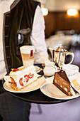 Kellner serviert Kuchen und Kaffee